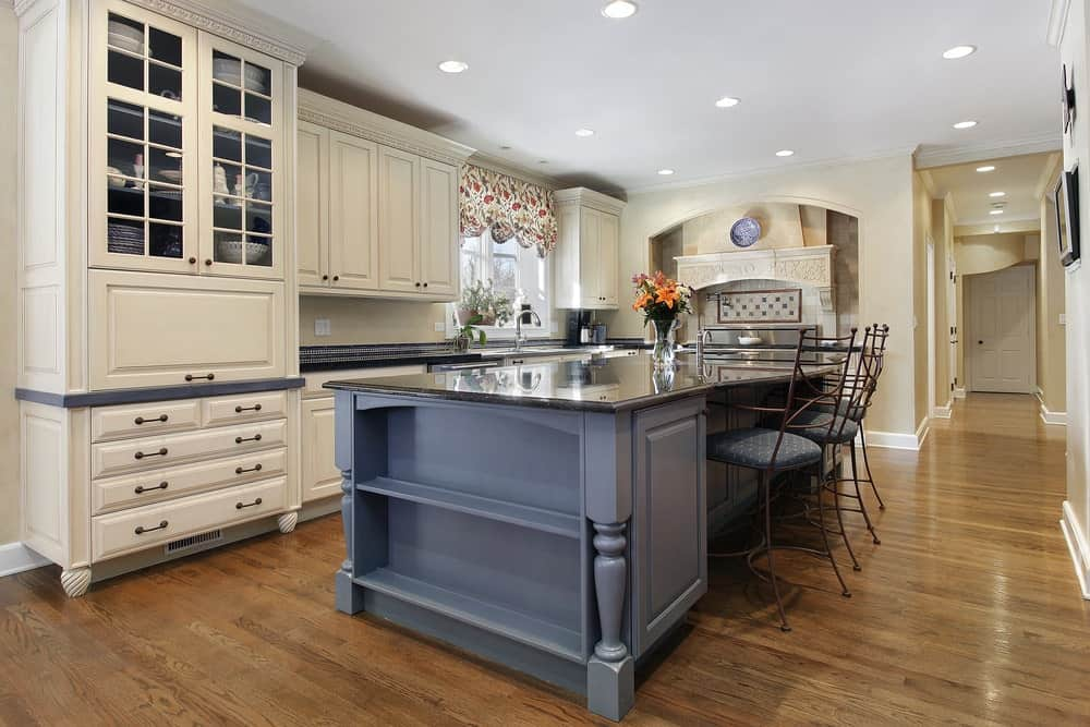 Gorgeous kitchen with white wooden cabinets, hardwood flooring and a breakfast island with dusty blue cabinet and shelves and metal chairs.