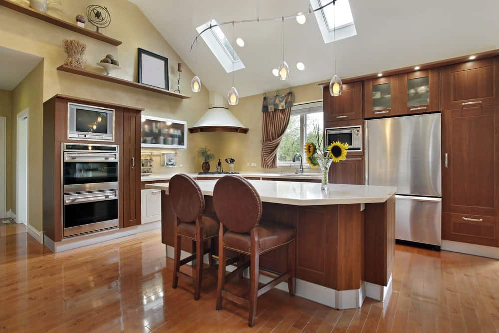 Cozy kitchen with pendant lights hanging on a vaulted ceiling, an island table with two cushioned chairs and brown wooden cabinets and shelves.