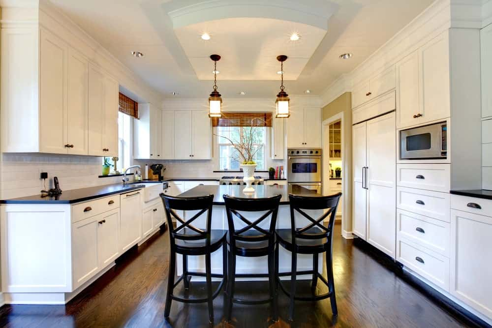 Sleek kitchen with white wooden cabinets, glossy white brick backsplash, elegant pendant lights, hardwood flooring and a breakfast island with three wooden chairs.