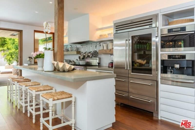 Gorgeous kitchen features a white island table topped with gray marble countertop seating white and brown counter stools, hardwood flooring and stainless steel appliances.