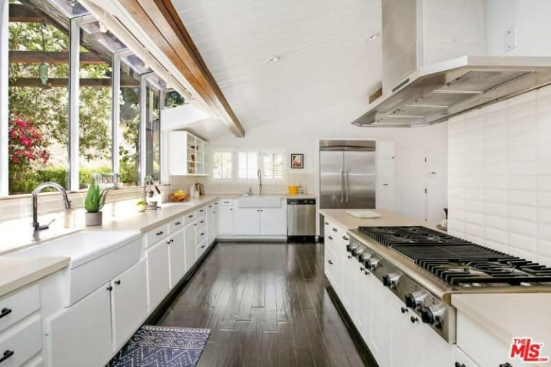 All white kitchen with wood accent, white cabinets and shelves, huge stove paired with stainless steel vent hood and a printed rug resting on a dark brown hardwood flooring.