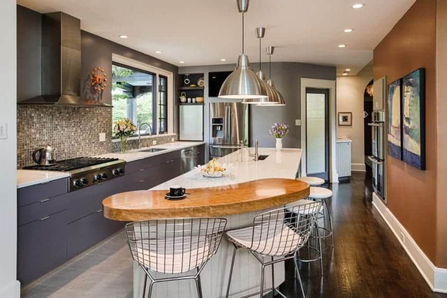 Contemporary kitchen with a white central island bar lined with a wooden counter that's paired with metal stools. It also has a dark gray cabinetry with white marble countertop and mosaic tiles backsplash.