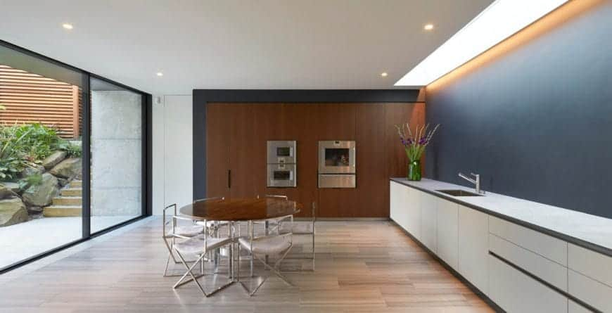 Sleek kitchen features a long white counter illuminated with a skylight along with strip light and recessed ceiling lights. It includes a round wooden table that matches the paneled walls.