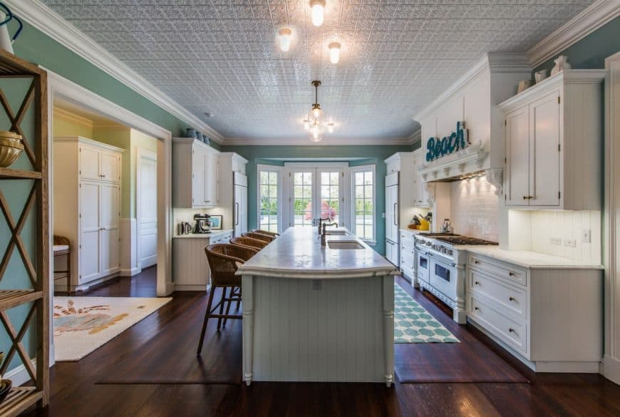 Spacious kitchen showcases a french door and white ornate ceiling fitted with pendants and light bulbs. It has an aqua shiplap breakfast island with dual sinks and chrome faucets.