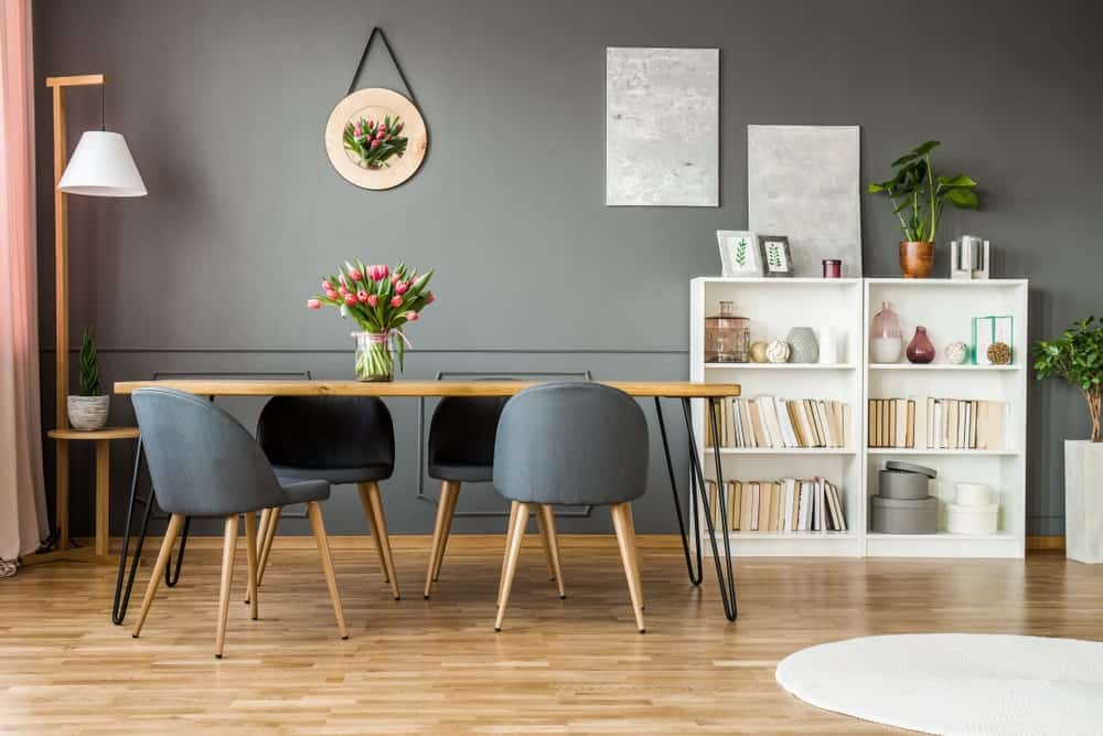 This dining room features wooden dining table paired with modern chairs along with white bookshelves. A pair of gray canvas and a tulip wall decor are mounted on the gray wall.
