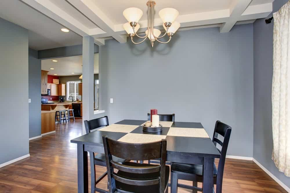 A simple dining space with a dark wood square dining table for four over a hardwood flooring and lighted by a lovely chandelier.