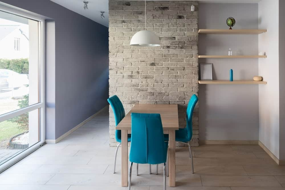 A small dining space features a gray brick wall with floating shelves next to it. It includes a light wood dining table accented with bright blue chairs over a wide plank wood flooring.