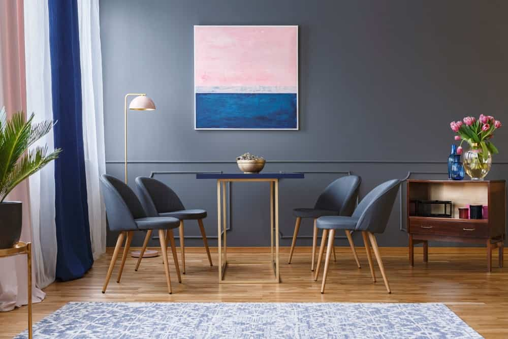 A bluish-gray wall designed with an abstract wall art canvas that perfectly matches the curtains. It has a small dining table for four that sits on hardwood flooring.