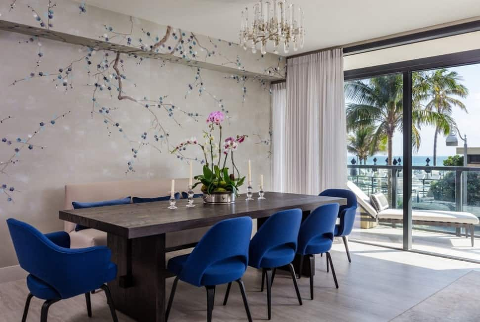 Transitional dining room accented with royal blue chairs and a nice twig wallpaper. A lovely crystal chandelier hung over a wooden dining table.