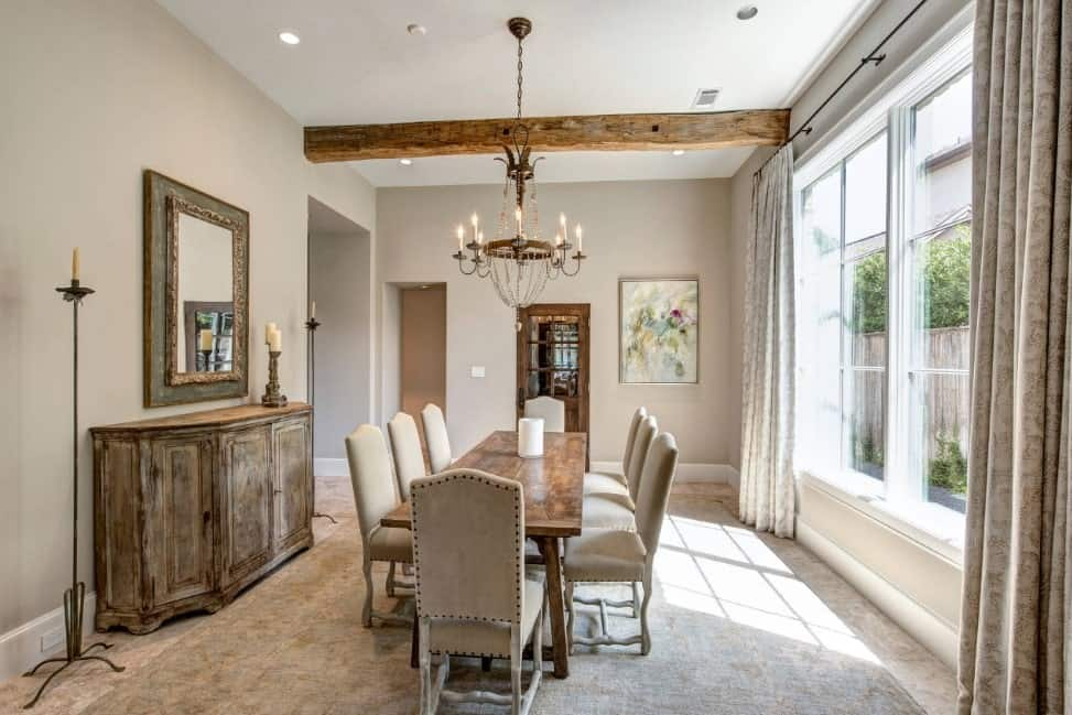 This dining room is accented with rustic wood elements from the dining table, buffet table and an exposed wood beam. A wrought iron chandelier from the white ceiling creates a timeless look.