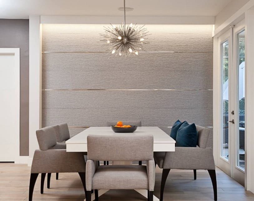 An eye-catching chandelier hung over a white dining table surrounded with gray chairs over hardwood flooring. Blue velvet pillows pop out from the neutral color scheme of the dining room.