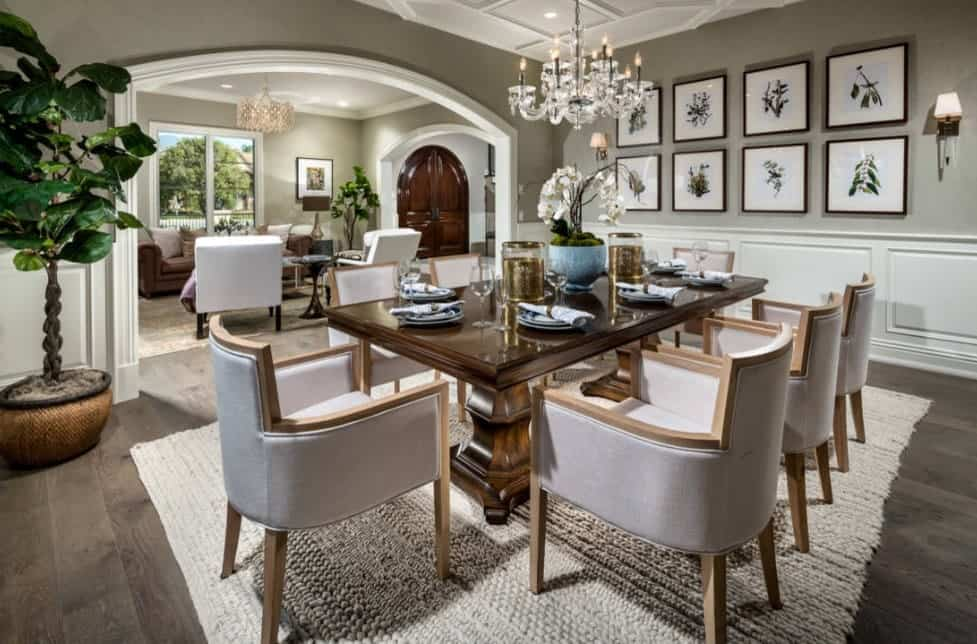 Gallery wall frames over white wainscoting accented this glamorous dining room. It has an arched wall opening that leads to the living room.