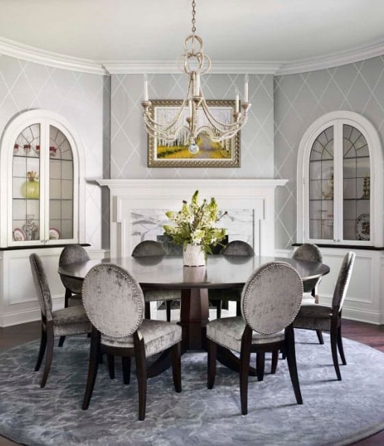 Elegant dining area features a diamond wallpaper and candle chandelier that hung over a round dining table. It is surrounded by gray velvet chairs over a round velvet rug.