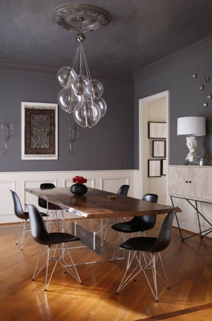Glimmer chandelier hung from a ceiling medallion over a rectangular dining table with black chairs. It has gray walls with white wainscoting and hardwood flooring.