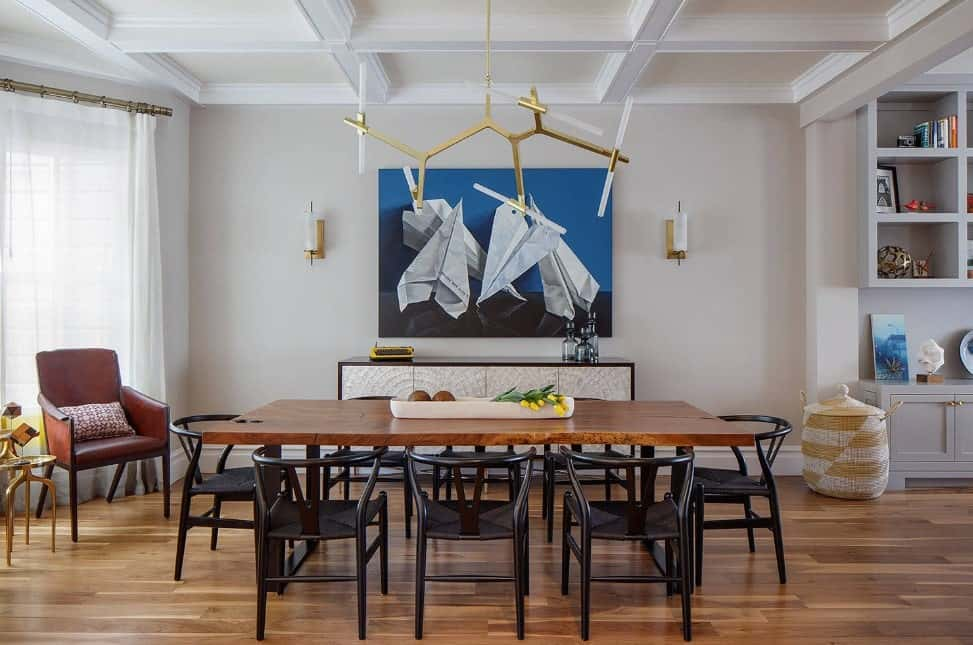 Artistic dining room decorated with a statement chandelier that hung from a white coffered ceiling and a paper airplane canvas mounted on the gray wall.