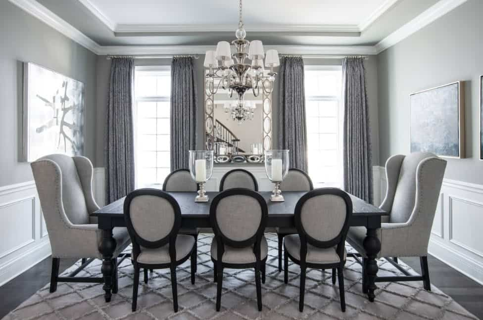 Gorgeous gray room showcasing a black wooden dining table surrounded with upholstered chairs over a diamond patterned rug. It is complemented by a fancy chandelier along with candle centerpieces.