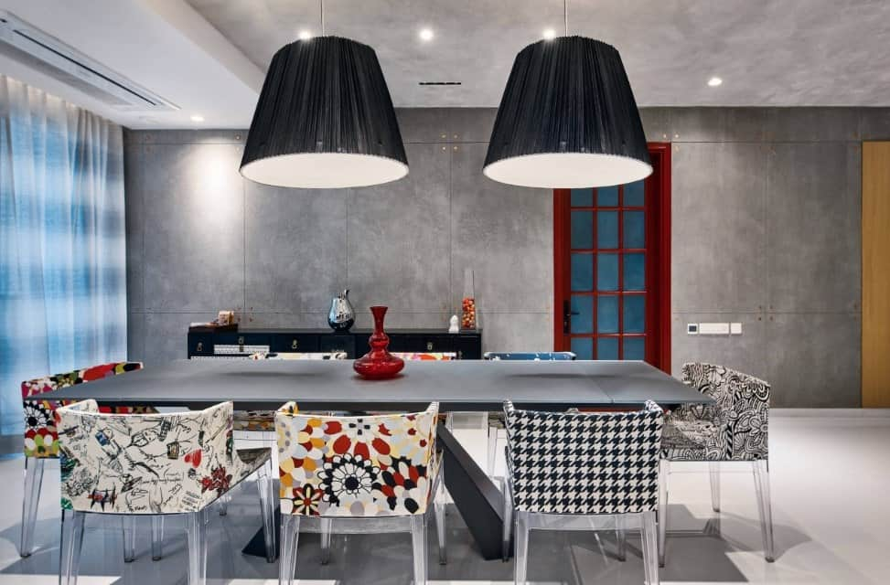 Huge black pendants illuminated the dining table with glass chairs covered with mixed designs creating an interesting look.
