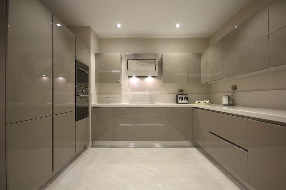 This kitchen offers magnificent gray kitchen counters and cabinetry, along with classy white tiles floors.