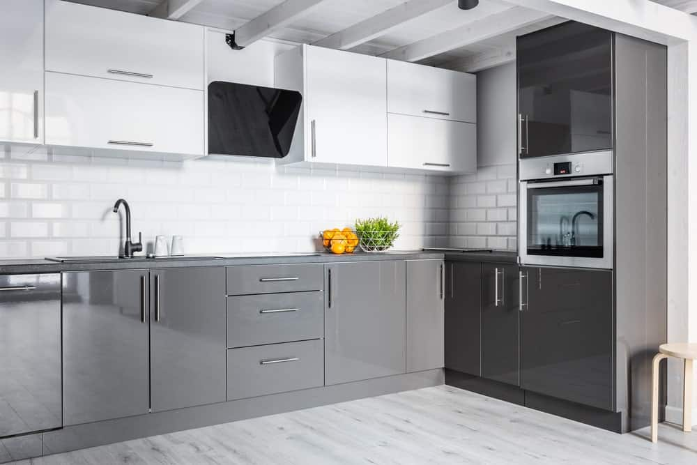 A close up look at this kitchen's handsome gray kitchen counters surrounded by white walls and cabinetry.