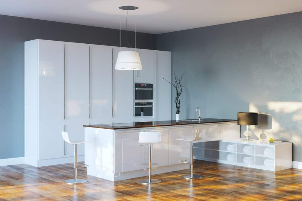 This kitchen boasts extremely attractive hardwood floors and gray walls surrounding the island with space for a breakfast bar.