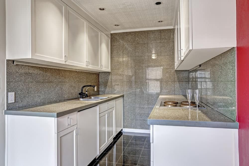 A kitchen featuring stylish gray tiles floors and walls matching the kitchen counters' countertops. The ceiling looks perfect together with the kitchen's style as well.