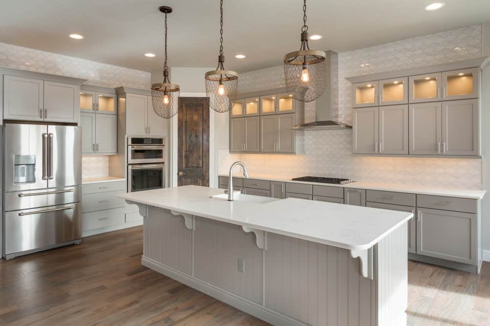 This kitchen features classy walls and hardwood floors, along with a regular ceiling lighted by recessed and pendant lights.