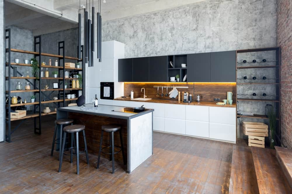 A single wall kitchen featuring gray walls and hardwood floors, along with a freestanding shelf on the left side of the breakfast bar.