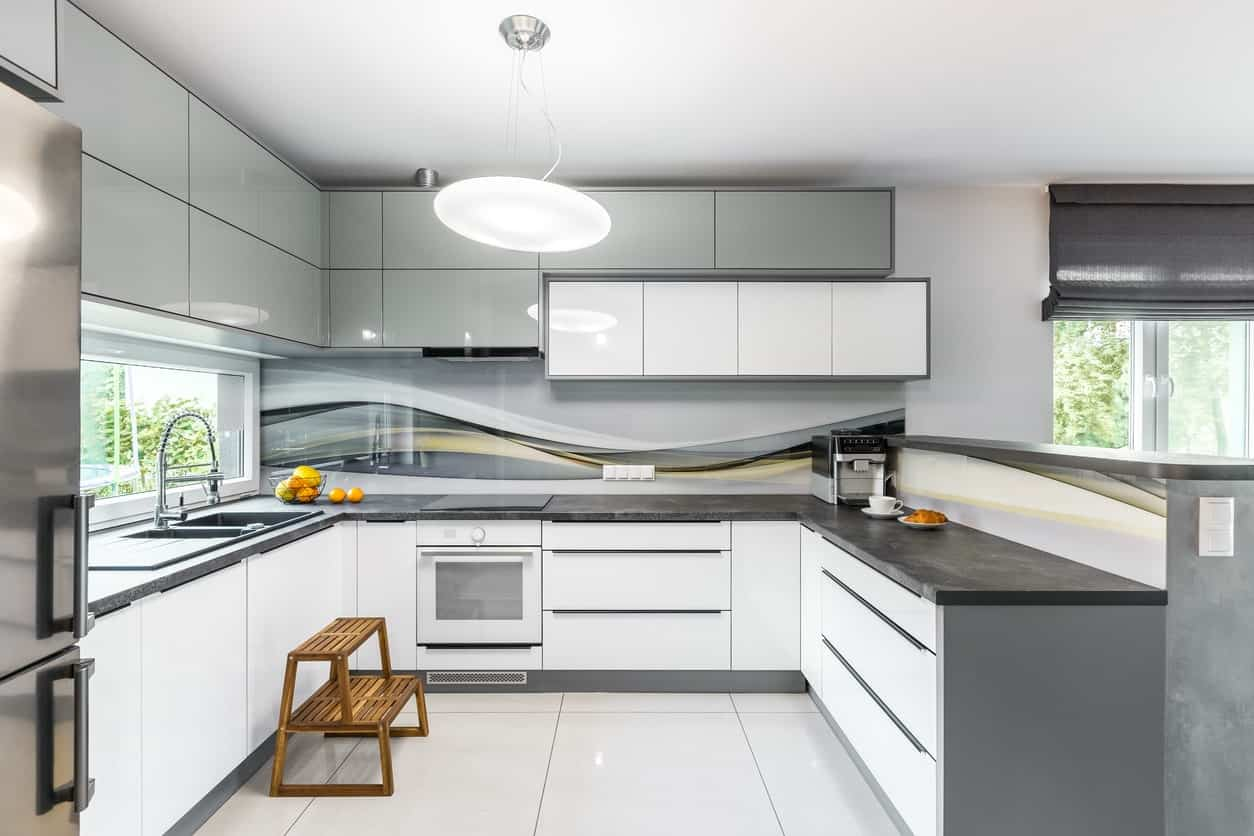Modern kitchen featuring white tiles floors and kitchen cabinetry with a gray shade and has stylish dark gray countertops.