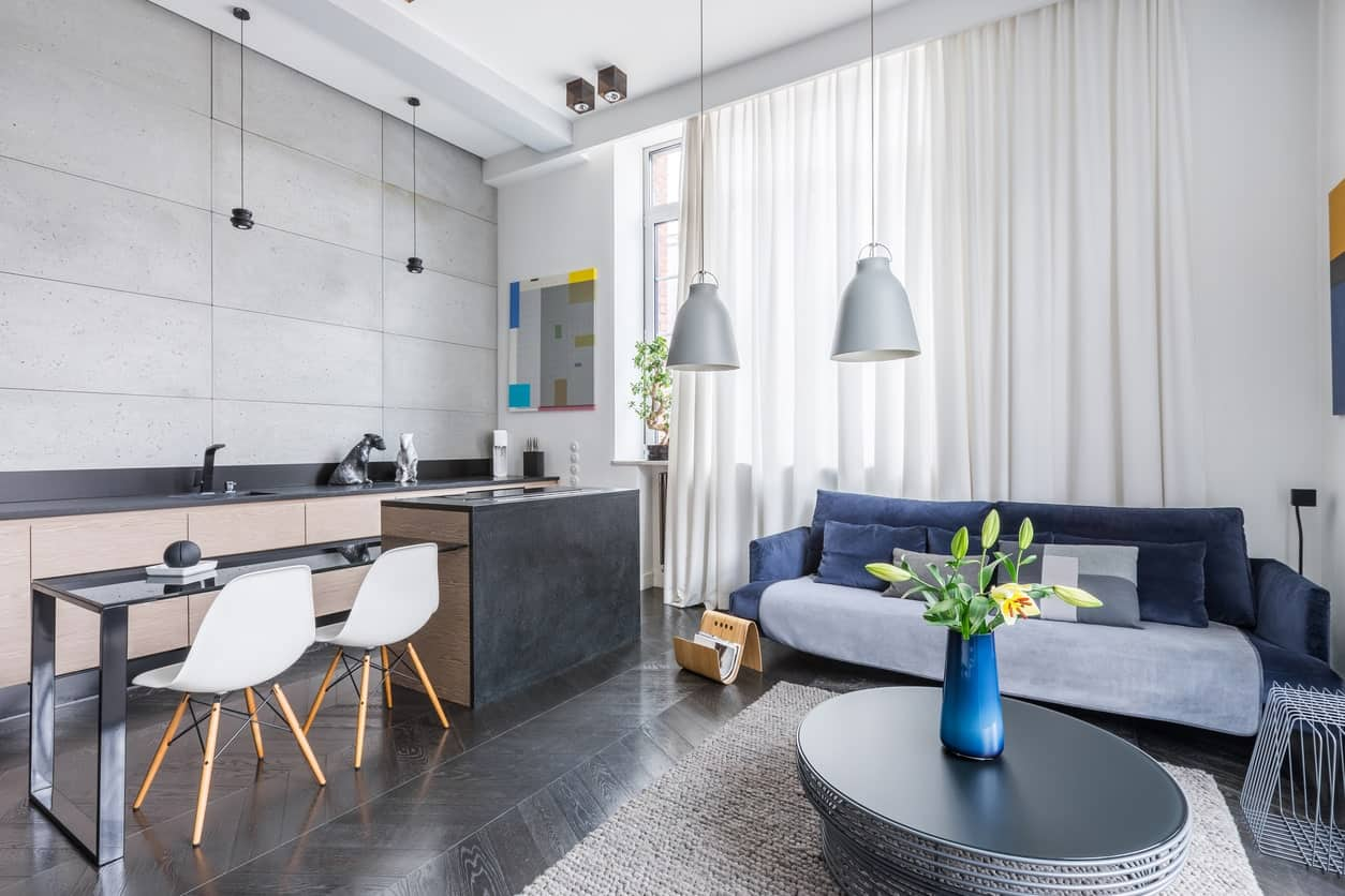 This kitchen offers a breakfast bar and a blue couch set on the herringbone hardwood flooring.