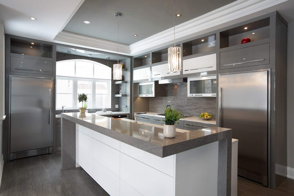 This kitchen offers a stylish center island set on the hardwood flooring and is situated under the tray ceiling lighted by fabulous-looking pendant lights.