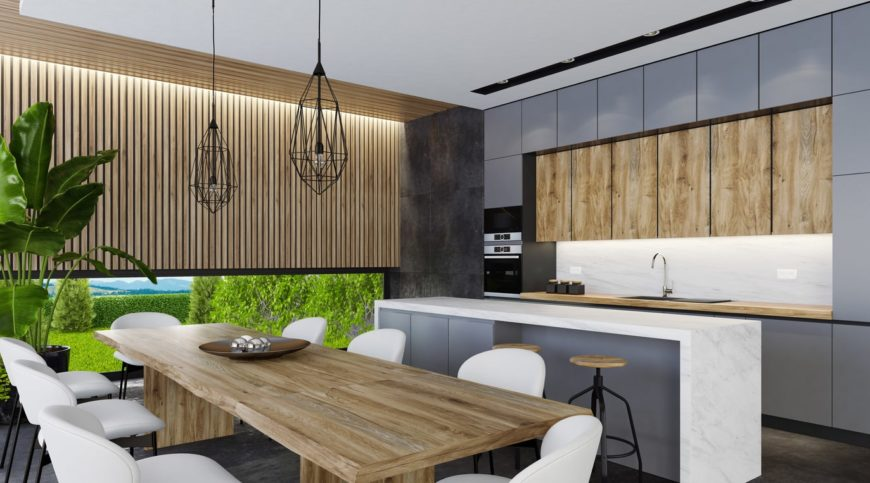 Single wall kitchen featuring a stylish wooden dining table set paired with white chairs and lighted by two pendant lights. The center island features a waterfall-style countertop with space for a breakfast bar.