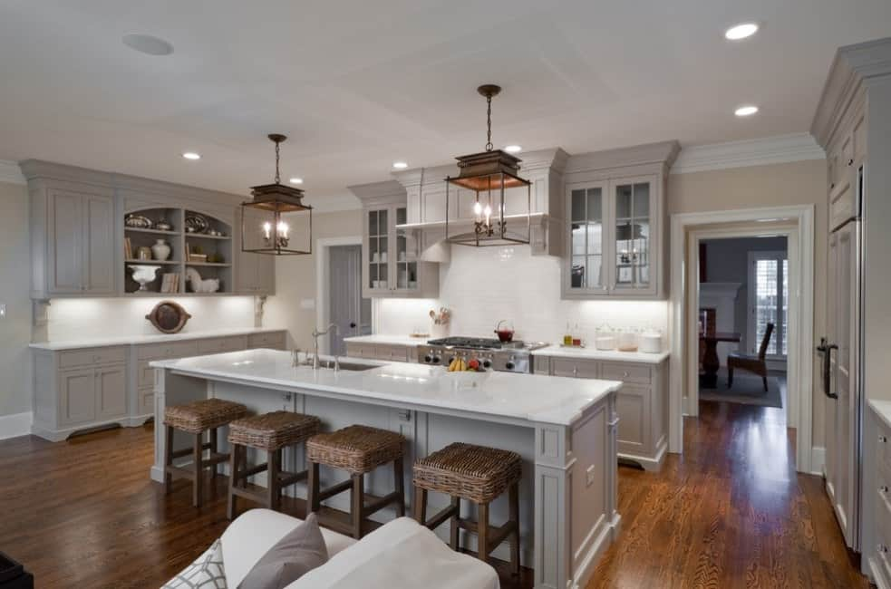 This kitchen boasts a large center island with space for a breakfast bar featuring white marble countertop similar to the kitchen counters'. The room is lighted by pendant and recessed lights.