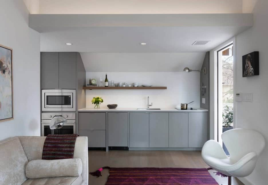 A single wall kitchen boasting a sitting area and an area rug covering the hardwood flooring. It also features gray kitchen counters and a built-in shelf.