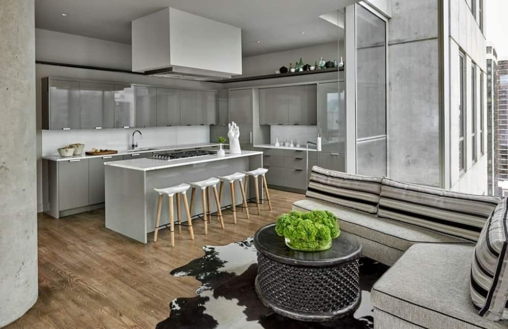 This kitchen boasts gray cabinetry and kitchen counters. It also has a breakfast bar and a sofa set with a center table on top of a stylish rug.