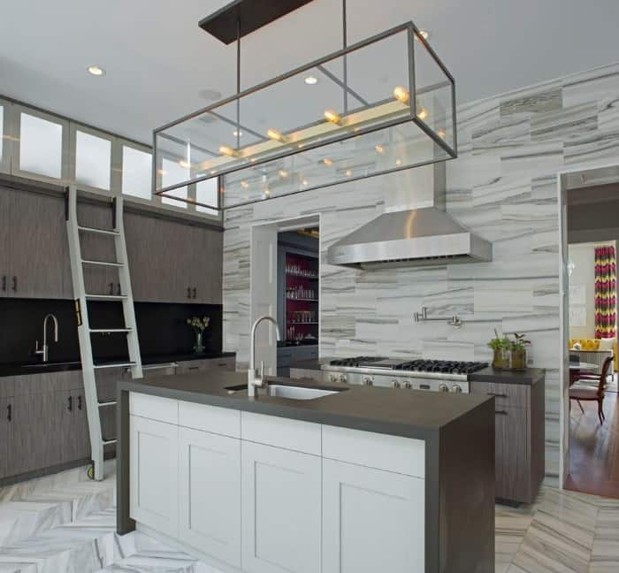 Kitchen with a tall ceiling and herringbone tiles flooring. It also features stylish walls and kitchen counters with a strong black backsplash.