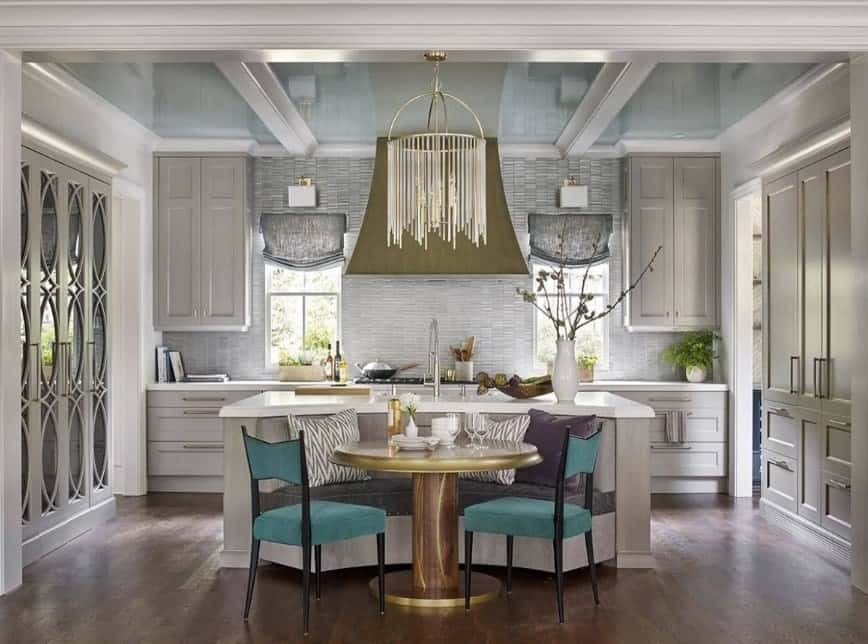 Single wall kitchen with a custom center island that is connected to the dining nook lighted by a stunning ceiling light hanging from a jaw-dropping ceiling.