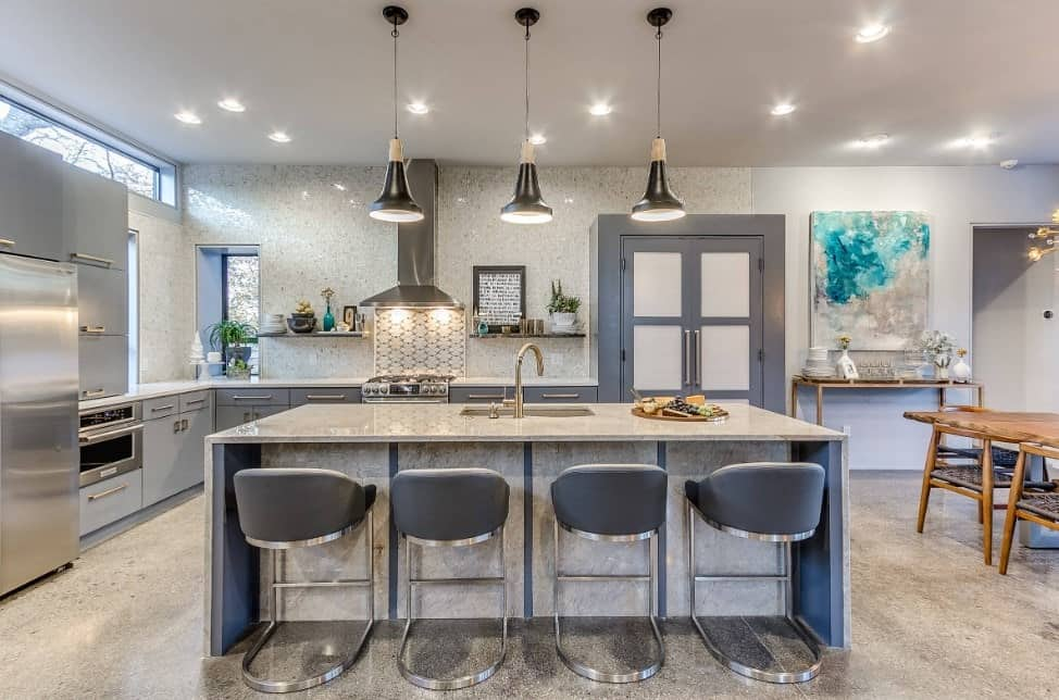 L-shape kitchen featuring a luxurious center island and breakfast bar lighted by pendant lights and is set on the home's elegant-looking flooring.