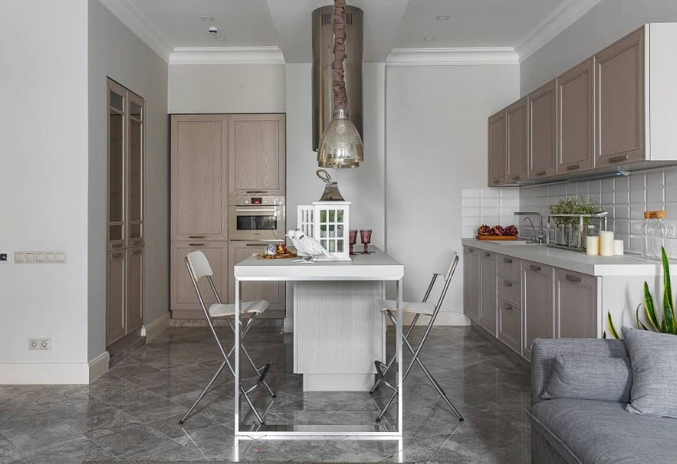 A small kitchen featuring gray tiles flooring and light gray walls. There's a center island with space for a breakfast bar lighted by attractive pendant lights.