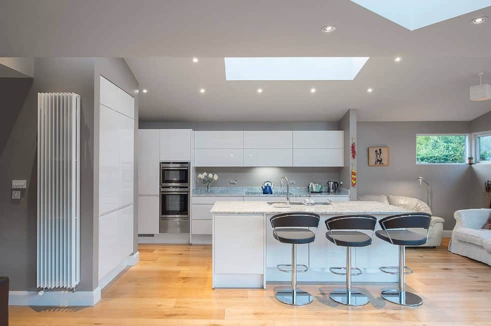 This kitchen offers a center island with marble countertop and has a breakfast bar for three under the regular ceiling featuring a skylight.