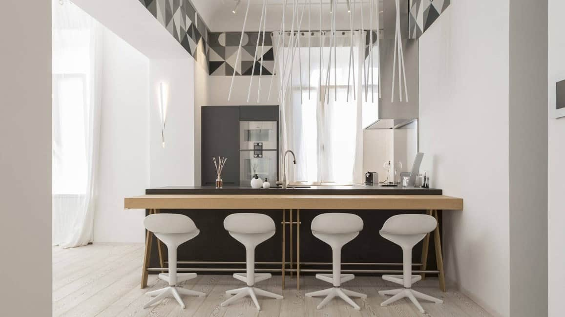 This kitchen has a very stylish design and also features a stunning ceiling lights and decors hanging from the tall ceiling.