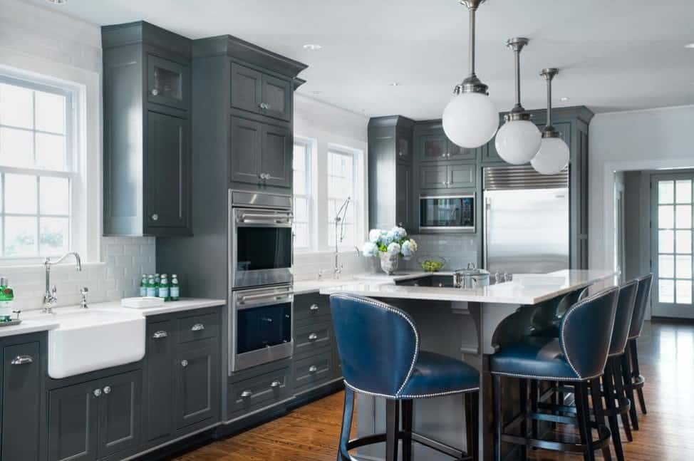 A kitchen with gray cabinetry and kitchen counters. It also features hardwood floors and a white ceiling, lighted by three pendant lights just above the breakfast bar.
