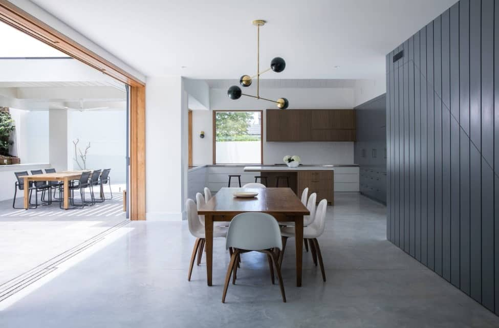 Spacious kitchen featuring gray floors and walls. It offers a breakfast bar and a dining table set lighted by a gorgeous ceiling lighting.