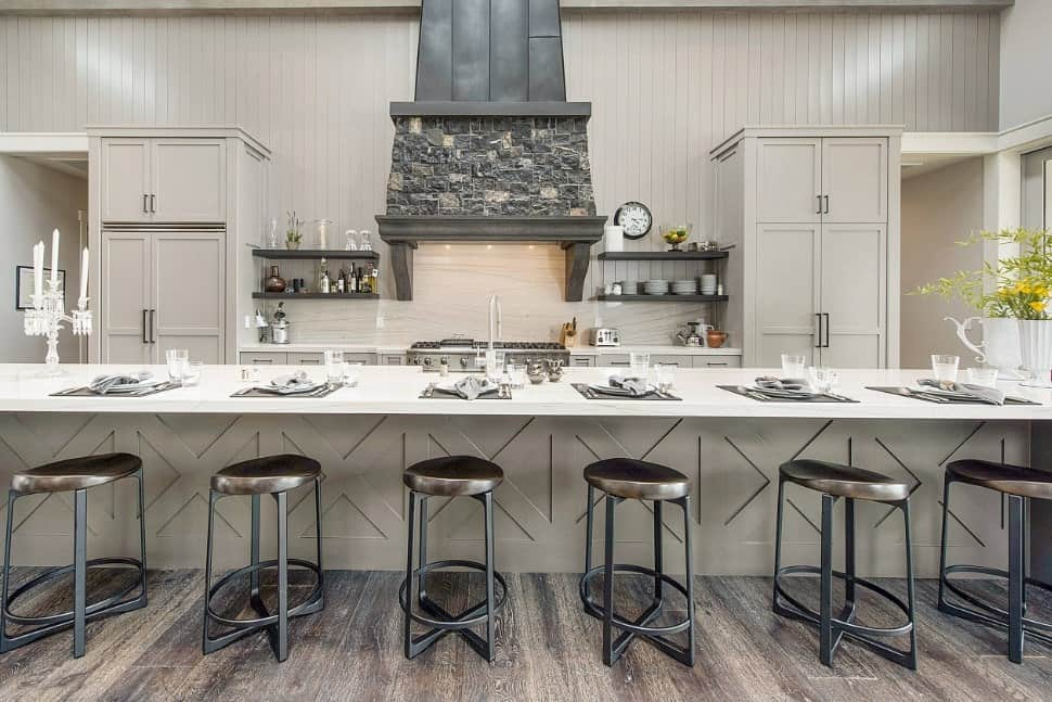 A single wall kitchen boasting a large center island with a breakfast bar set on the hardwood flooring. The bar features a smooth white countertop.