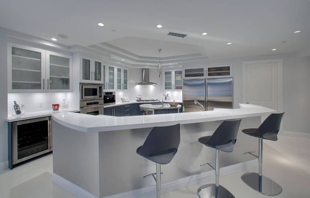 Modern kitchen with a custom breakfast bar with modern bar stools and a smooth white countertop. The area features white floors and a tray ceiling.