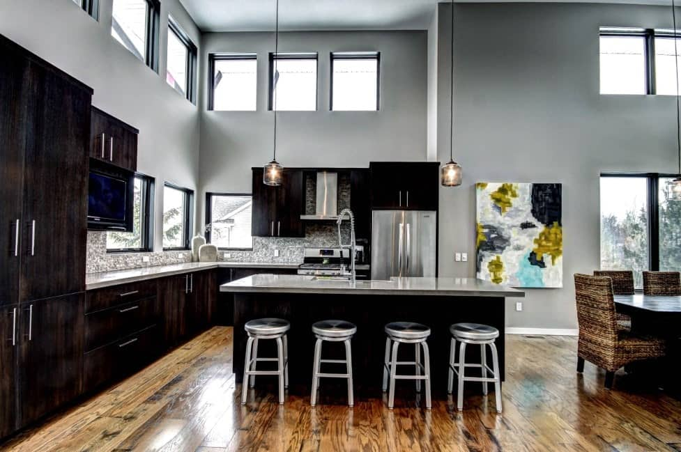 Contemporary kitchen featuring stylish kitchen counters, center island and cabinetry. There's a breakfast bar set on the hardwood flooring. The area has multiple glass windows and a tall ceiling.