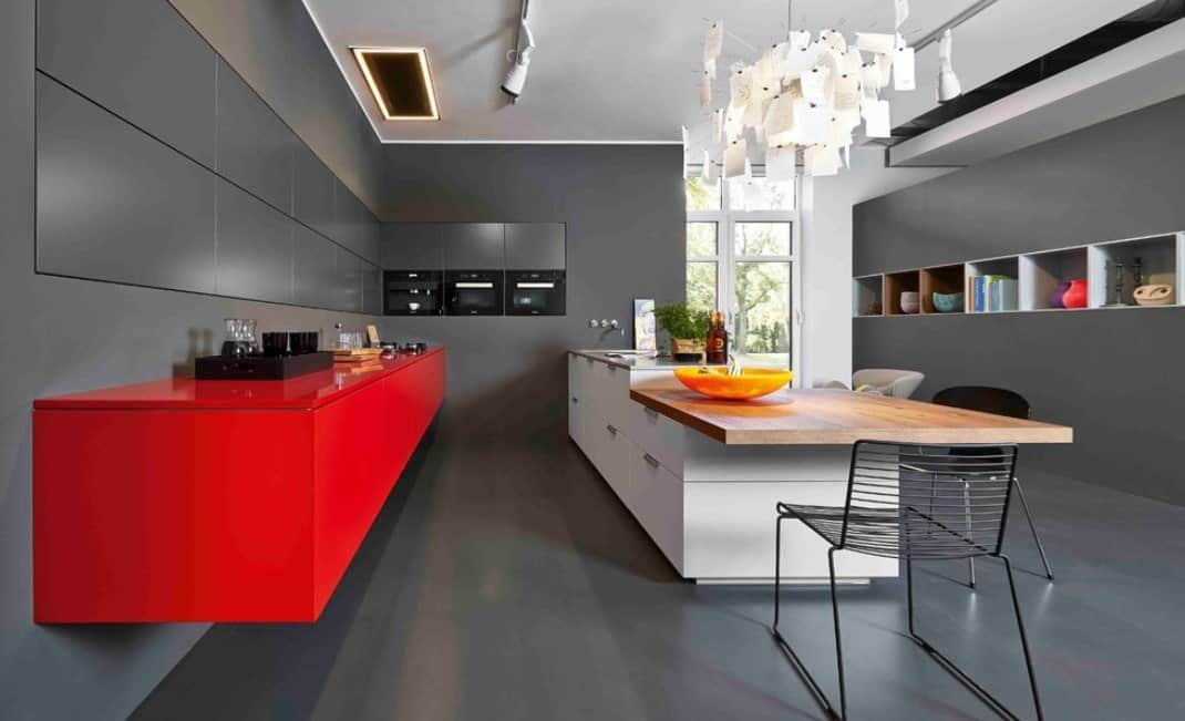 Contemporary kitchen featuring gray walls and a red floating vanity kitchen counter. The breakfast bar is lighted by stunning ceiling lights.