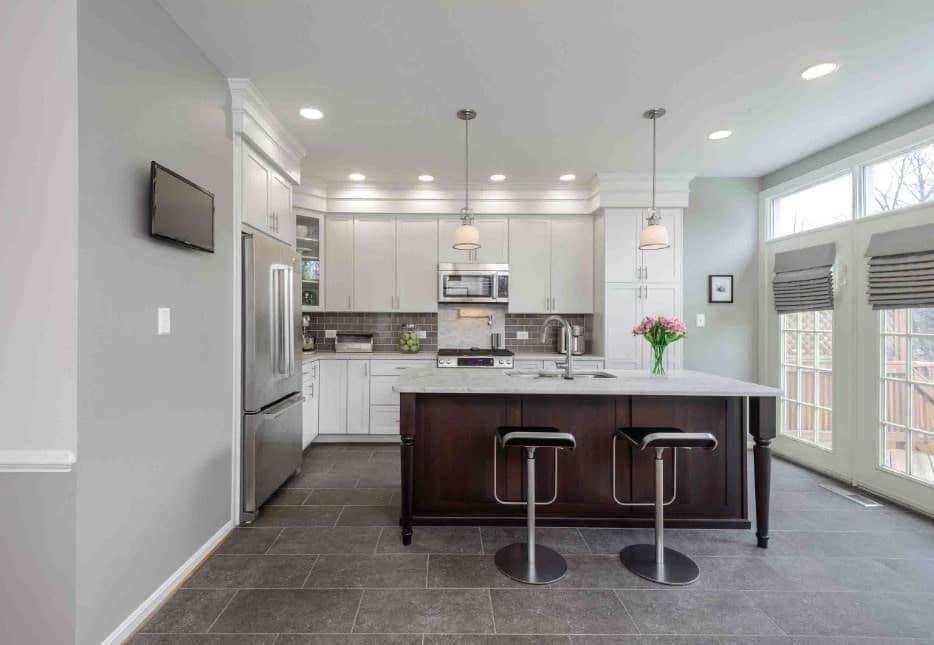 L-shape kitchen featuring gray tiles floors and walls, along with a ceiling featuring pendant and recessed lights. There's a center island providing space for a breakfast bar.