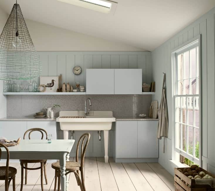 This kitchen boasts gray walls matching the gray kitchen counters and cabinetry. The shed ceiling features a skylight.
