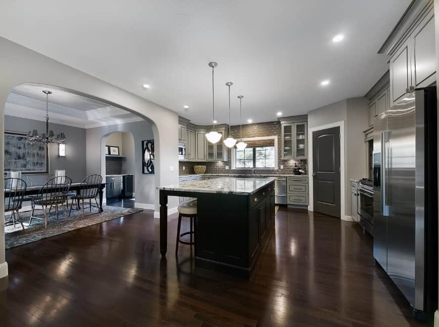 Large kitchen featuring a large center island with a marble countertop. It is set on the home's hardwood floors and is lighted by pendant lights.