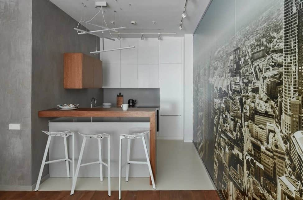 Small kitchen featuring a very attractive wall design. It also features a breakfast bar and gray kitchen counters, lighted by track lights.